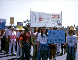 """People posing with a sign which reads """"Get the Cops out of our Bars!-- San Diego Gay Rights Committee"""", with a drawn Lambda icon and a drawing of a high heel boot kicking a cop out of a gay bar. Another sign reads """"Here to Stay-- Dyke Patrol International""""."""