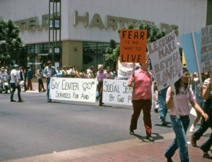 "Image of people marching on the street flanked by signs that read ""Gay Center for Social Services-- Services by and For Gay People"", ""Fear is no Way to Live"", and ""Lesbians make better lovers""."