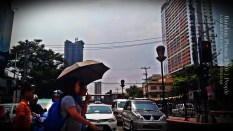 Umbrella. A group of people crosses the street in Manila. The heat in the city can be very scorching and although umbrellas can protect people from the sun's rays, the rising heat index is another issue.