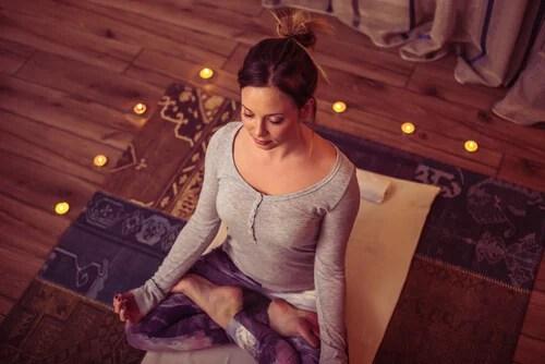 Mujer meditando entre velas