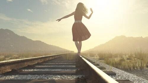 Mujer en una vía de tren confiando en la suerte y la ley de la atracción