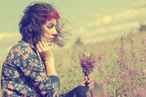Mulher triste olhando um buquê de flores