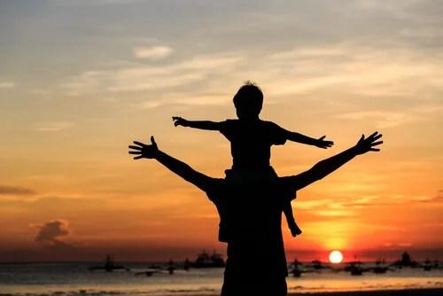 Hijo aprendiendo sobre los hombros de su padre en la playa