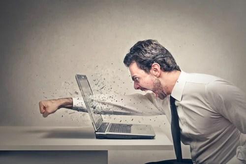 Hombre con agresividad golpeando ordenador