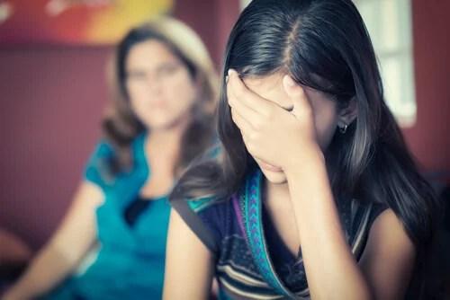 Chica adolescente con la mano en la cabeza sintiéndose rechazada por su madre