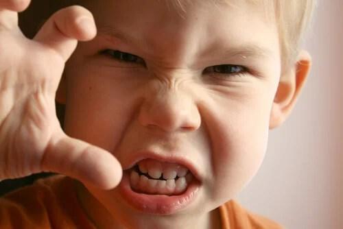 Niño con la cara de agresivo y con mano en posición de garra