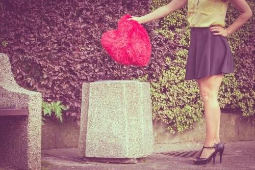 Mujer tirando un corazón a la basura