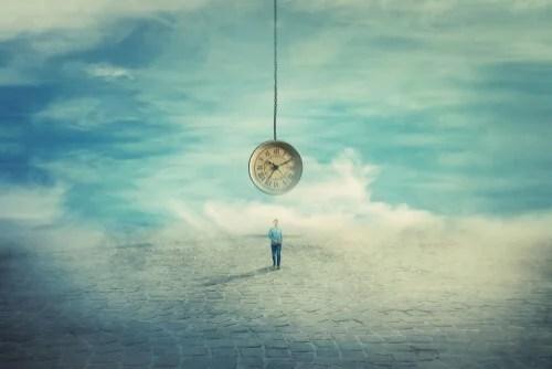 Hombre bajo reloj simbolizando la procrastinación y su relación con la ansiedad