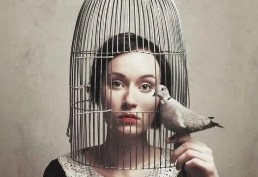Mujer con la cabeza metida en una jaula simbolizando cuando callamos más de lo necesario