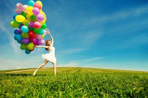 Mujer con globos de colores en el campo