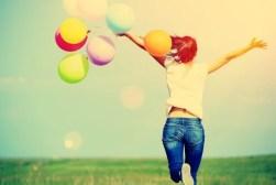 Mujer feliz con globos de colores