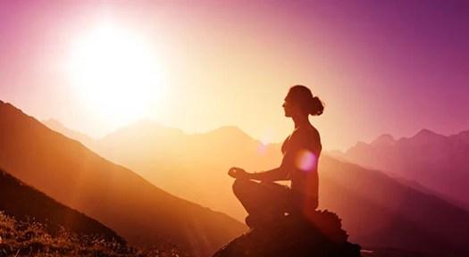 Mujer meditando en una montaña al amanecer intentando conectar con su abundancia