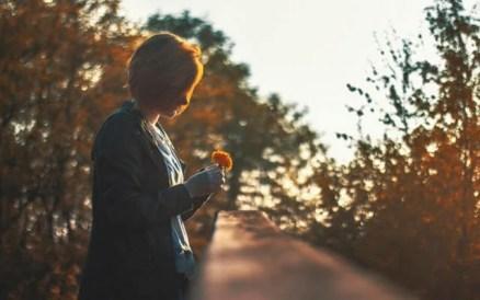 Mujer mirando una flor al atardecer para vencer la desesperanza