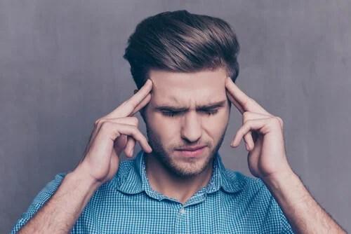 Hombre sintiendo rencor con las manos en la cabeza