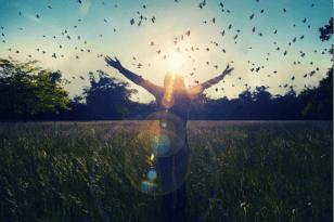 Mujer con los brazos abiertos disfrutando de su felicidad
