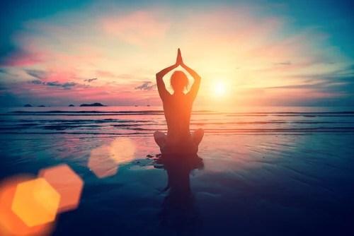 Mujer haciendo yoga en el mar