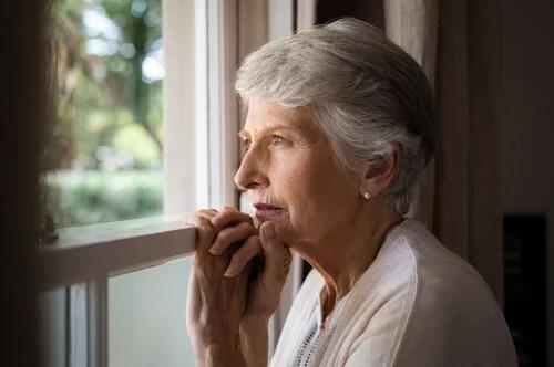Mujer mayor mirando por la venta