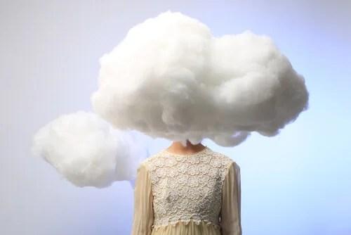 Mujer con una nube en la cabeza que representa los sesgos cognitivos