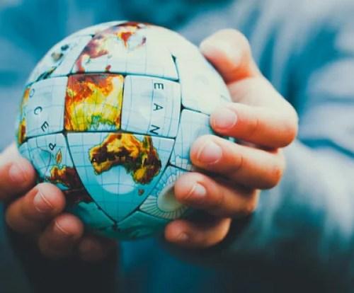 Manos con la bola del mundo para representar el trauma colectivo