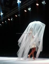 Abito corto a balze stile Charleston su una pioggia di tulle e cristalli tenuta da un suggestivo ombrellino bianco