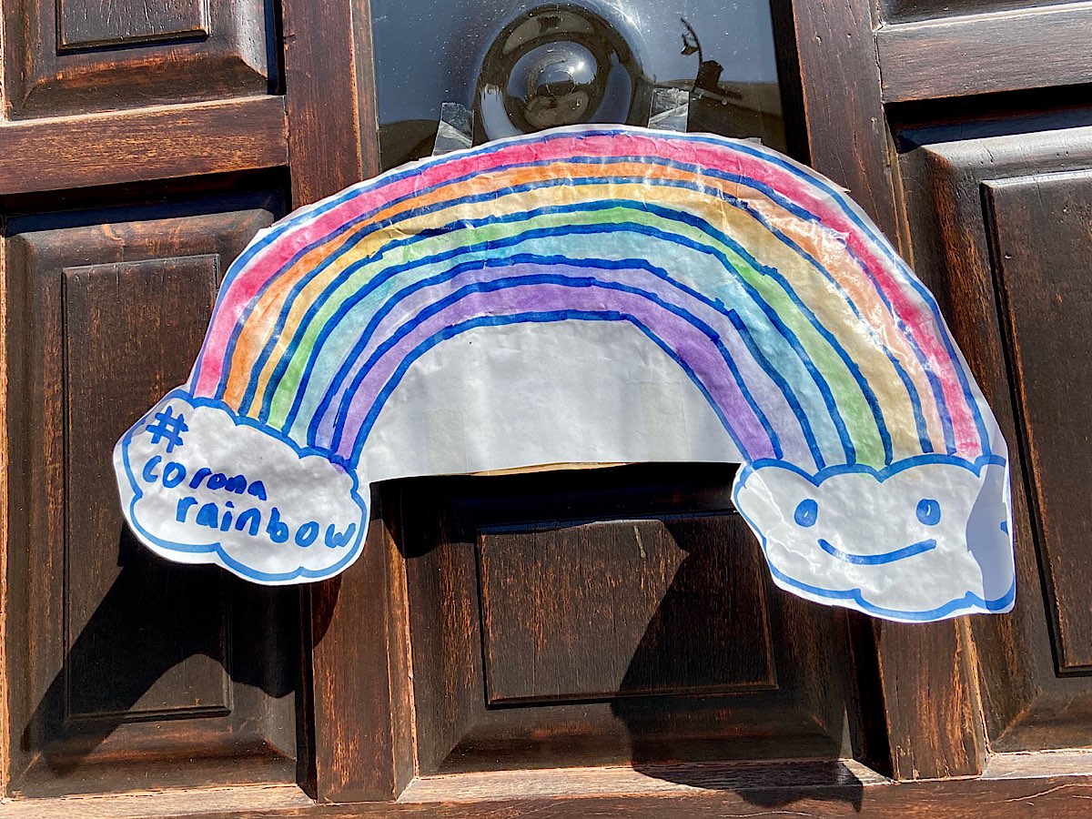 A rainbow that's cut out of paper and pinned onto a door. One end of the rainbow is in a cloud that says '#coronarainbow ' and the other side has a smiley face in a cloud