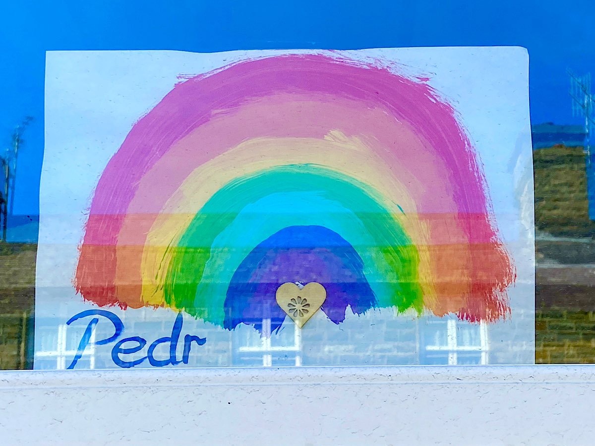A rainbow in a window with Pedr in the corner and a small wooden heart in the middle