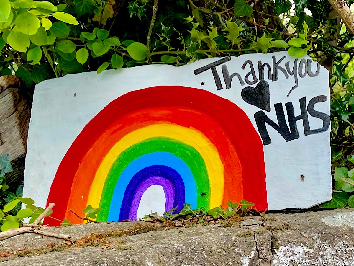 Thank you NHS is written in the corner of a large rainbow painted onto a large white piece of rock by the side of the road