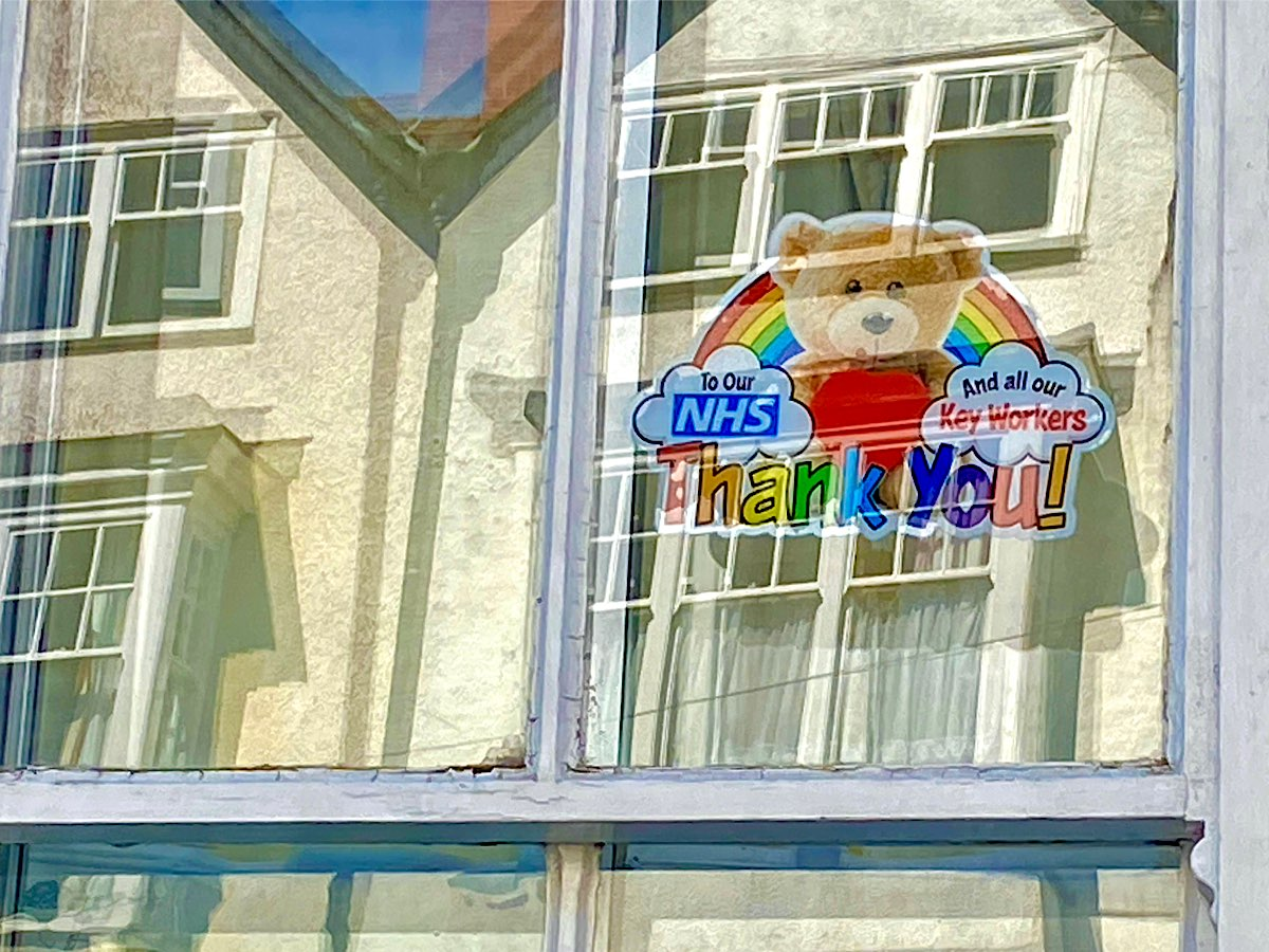 This is a printed image with a big teddy holding red heart sitting in front of a rainbow, there are clouds at either end, one says To our NHS and the other says And all our Key workers and at the bottom its says Thank You. Unfortunately this picture is not a good one