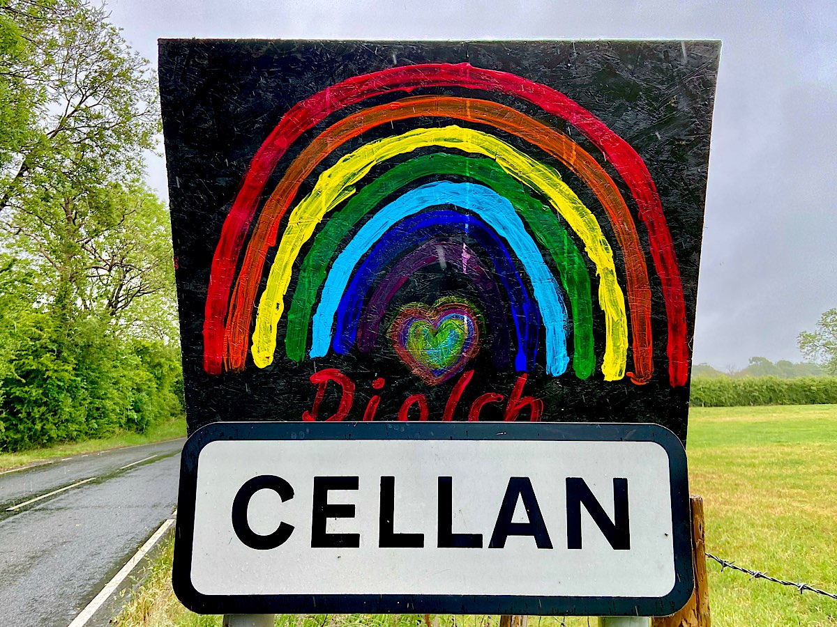A rainbow painted on black board, says 'diolch' underneath and a small heart shaped also rainbow coloured heart sits under the rainbow. It is mounted onto the sign for Cellan