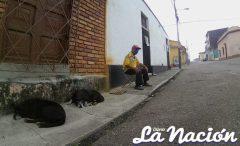 Una persona de tercera edad con tapabocas se sienta frente a su vivienda. (Foto/Johnny Parra)