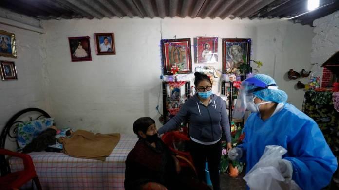 La doctora Delia Caudillo, a la derecha, da recomendaciones médicas a Modesta Caballero, de 82 años, a la izquierda, quien estuvo acompañada por su nieta, después de que personal médico le administró a Caballero una prueba de diagnóstico de coronavirus el jueves 19 de noviembre de 2020 en su casa en la demarcación Venustiano Carranza, en la Ciudad de México. REBECCA BLACKWELL AP