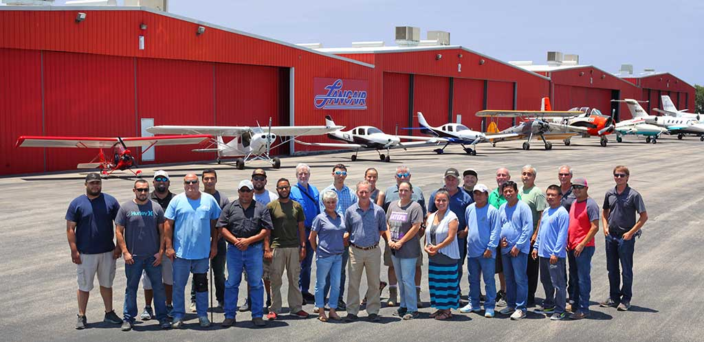 Lancair International staff in front of hangars