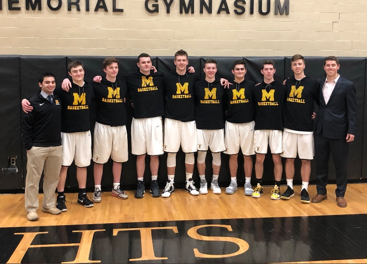 McQuaid+Varsity+Basketball+Knights+take+a+picture+with+head+coach+Jack+Leasure%2C+%2704%2C+on+senior+night.+