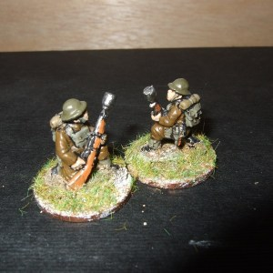 2 men kneeling firing rifle grenade