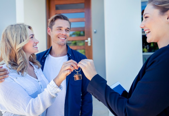 A property manager handing a set of keys to new tenants renting a property.