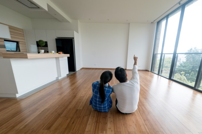 young-couple-sitting-on-wood-floor-of-empty-apartment-imagining-decor-as-new-tenants