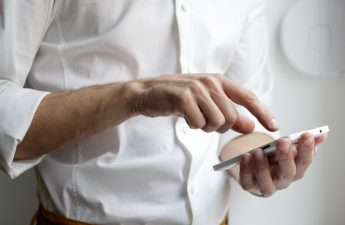 man-in-white-formal-shirt-using-smartphone-cropped-below-shoulders