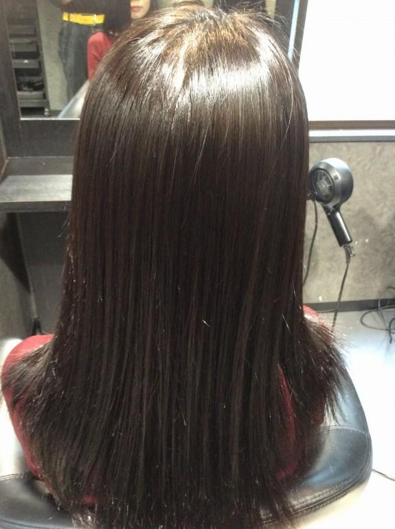 縮毛矯正施術後の画像です。女性が美容室の鏡の前で鏡の方を向いて座っています。その後姿を近くから写真に撮りました。根元から毛先までツルツル、ピカピカの美しい髪の毛です。天使の輪が眩し過ぎます。柔らかく水分をタップリ含んだ髪の毛の状態です。とても美しい状態の髪の毛です。