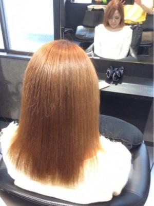 金髪の女性の後ろ姿の写真です。少し斜め右側から写真に撮った。毛先はシッカリ伸びています。直毛の人の奇麗な状態で頭頂部には天使の輪が広がっています。柔らかそうな感じです。美容室の鏡の前に座っています。鏡にはご自身が写っています。背後にアイパッドを持った美容師も写っています。