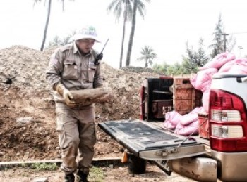 With professional caution and care, EOD Team Leader Hoang Duc Long loads the plaster-coated naval shell onto his team's truck for transport to the demolition site.