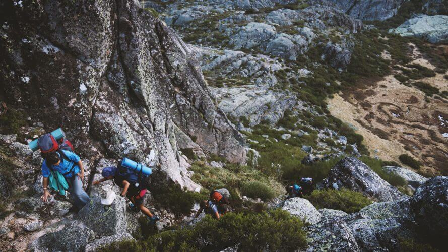 A group of trekkers climbing a steep mountain