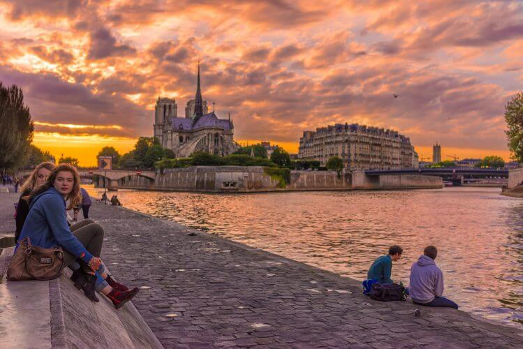 An image of a few people relaxing by on the banks of the Seine
