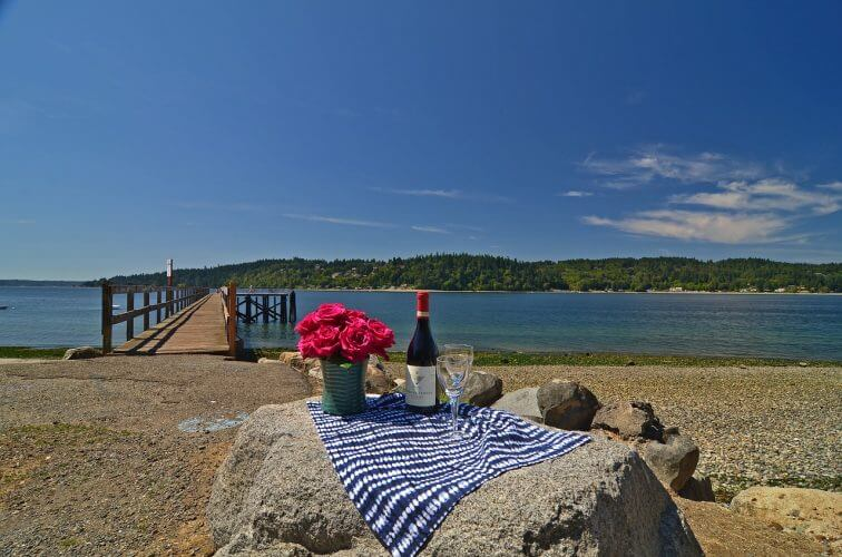 A setting featuring wine glasses facing the water at bainbridge island