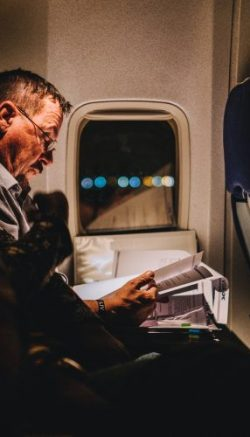 A person is seen reading a book during a long flight in this image