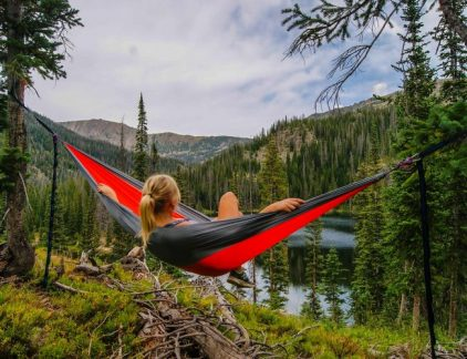 An image of a girl on a hammock overlooking a lake