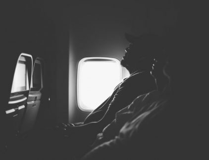 A few people getting some sleep on a plane is shown here