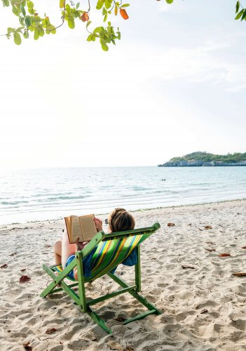 A person getting some reading done on the beach