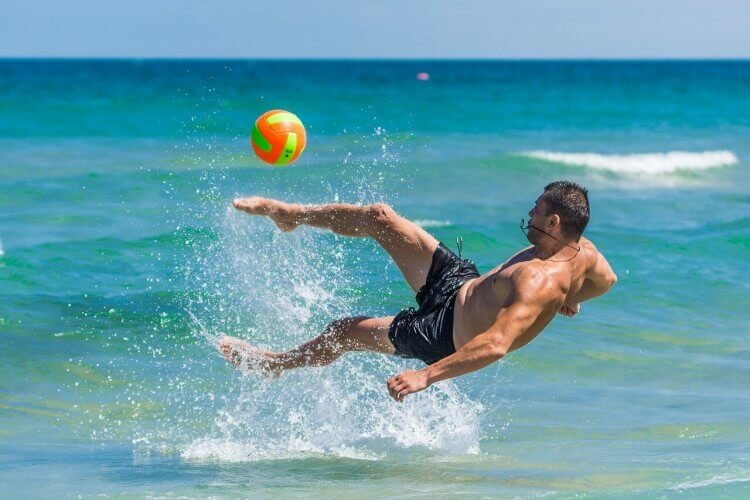 A man playing with a volleyball in the water