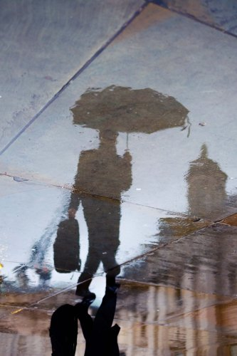 A reflection of a person carrying a windproof umbrella is seen here