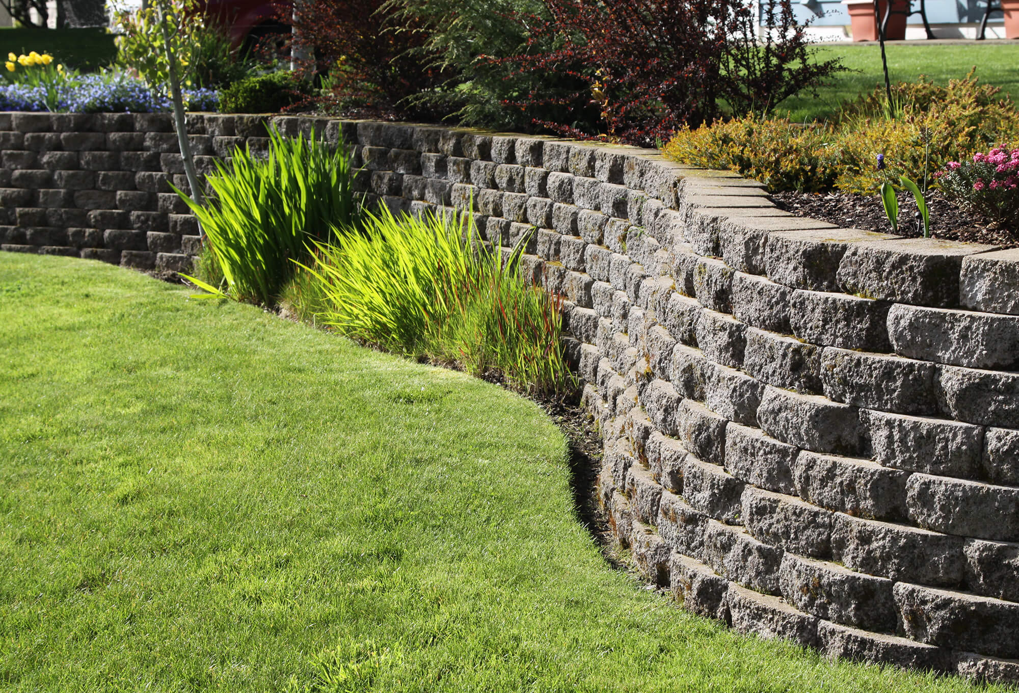 curved retaining wall with rounded cementitious stacked stone surrounding garden with green grass and shrubs
